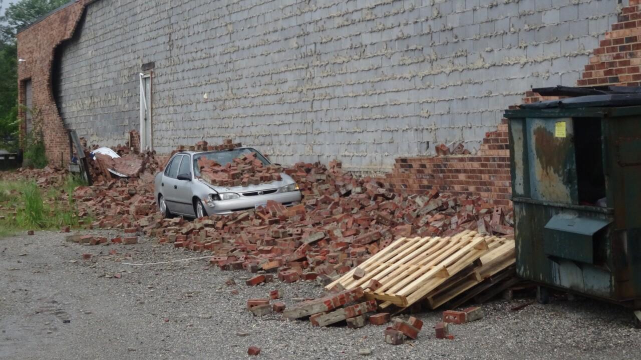 Brick wall tumbles down onto vehicle duringstorm
