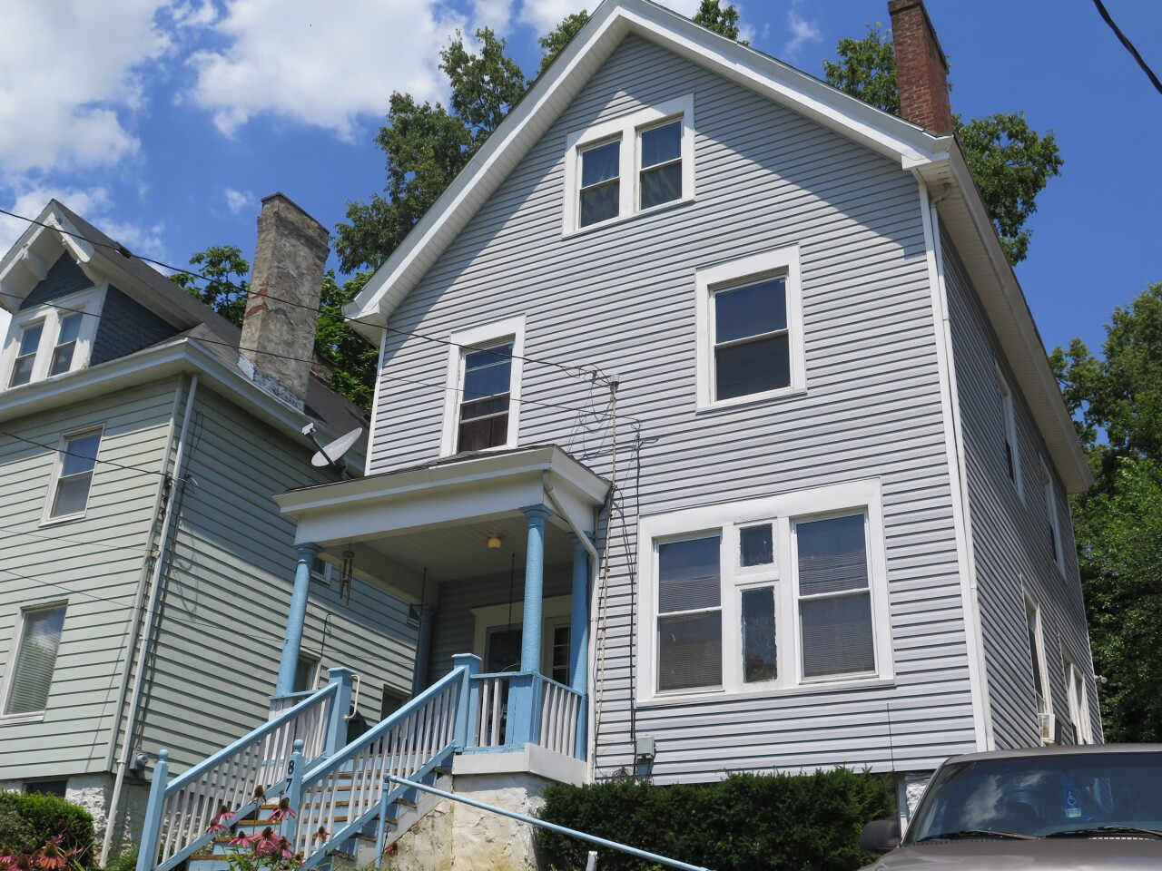 Robert McCrary's Avondale home is pictured in this photograph. it has grey siding and white and blue trim. A railing leading up to the front steps is visible in the photo.