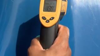 Heat gun taking temps of playground equipment