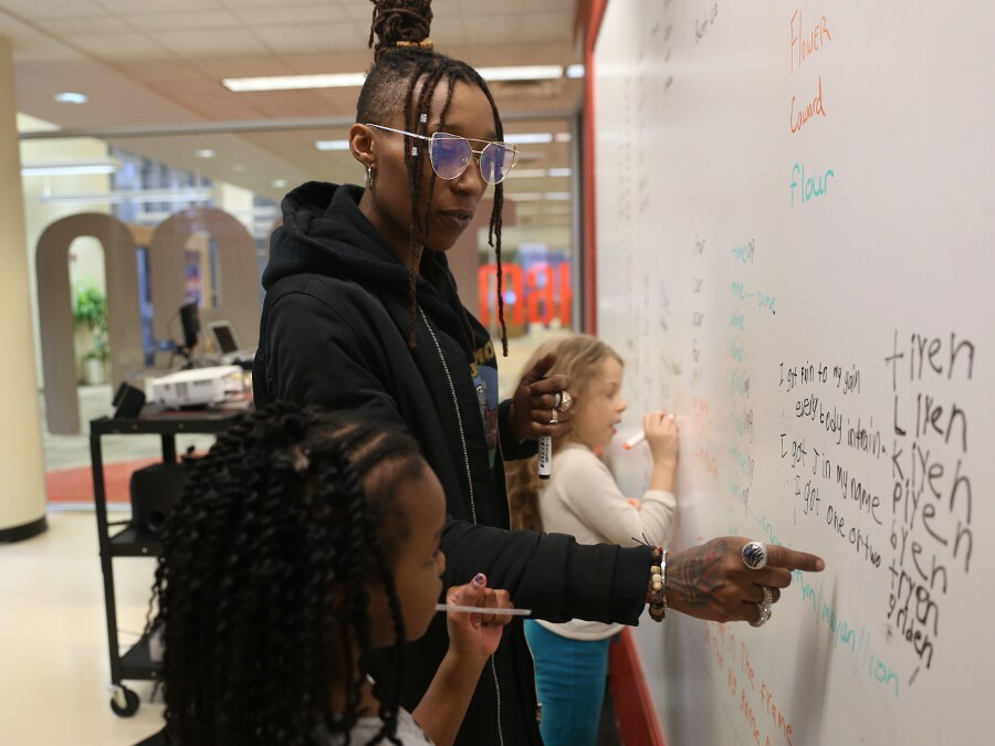 Siri Imani, standing and wearing glasses and a black sweatshirt, points at a white board to help two little girls find rhyming words as part of a Raising the Barz class in 2019.
