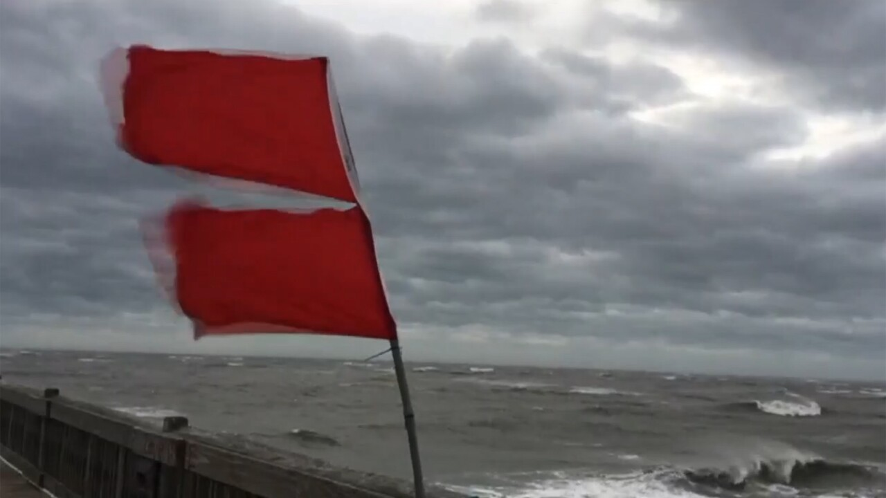 Red hurricane warning flags flying at the beach.