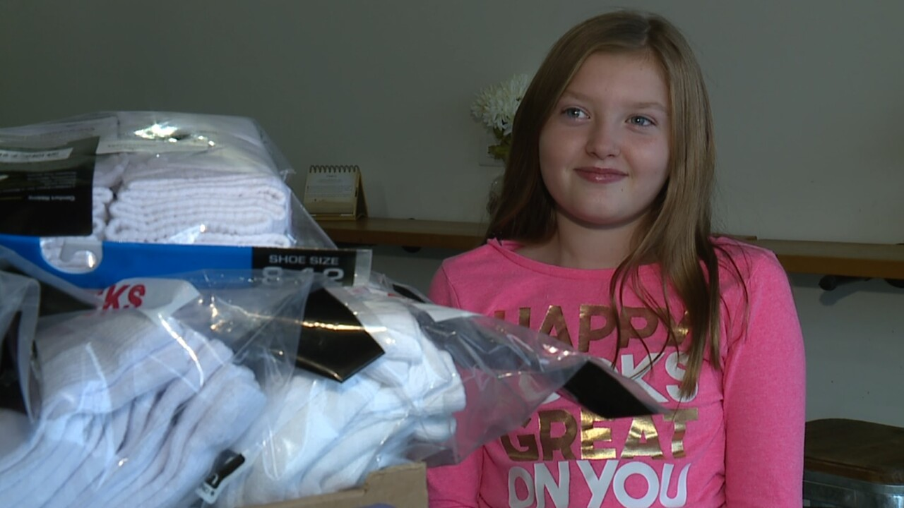 Young girl sitting next to pile of socks to be donated to homeless shelter
