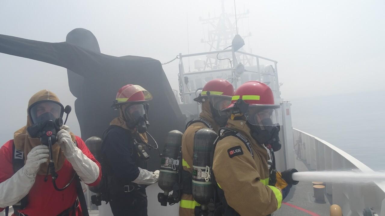 Coast Guard Cutter Benjamin crewmembers work to extinguish a vessel fire off the San Diego coast