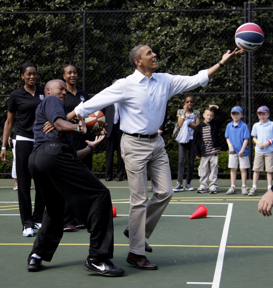 FILE - In this April 9, 2012, file photo, President Barack Obama plays basketball with former NBA basketball player Bruce Bowen during the annual White House Easter Egg Roll at the White House in Washington. Bidding was drawing to a close Friday, Aug. 16, 2019, for a basketball No. 23 Punahou School jersey believed to have been worn by President Barack Obama. Obama the wore that number during the 1978-79 school year in Honolulu. (Courtesy AP)