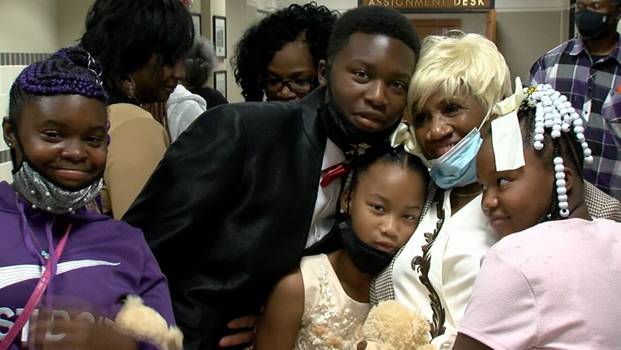 The Thompsons' four adoptive children pose for a picture with Karen Thompson's mom after the proceedings. The children and grandma have their masks pulled down and are all smiling.