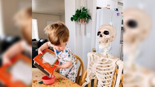Halloween lovers can relate to this toddler's obsession with a decorative skeleton