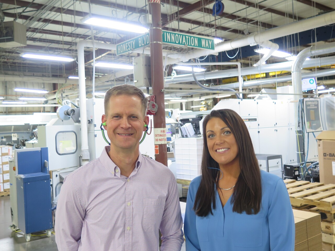 """Marcus Sheanshang, left, and Amanda Hall pose for a photo in JBM Packaging's manufacturing facility. They're standing below street signs that say """"Innovation Way"""" and """"Honesty Blvd."""""""