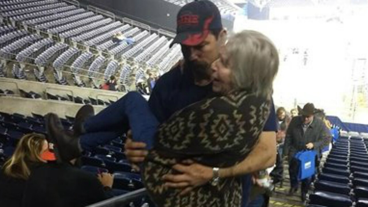 Photo of firefighter carrying elderly woman up stadium stairs captures hearts
