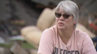 Woman survives flood by clinging to wood