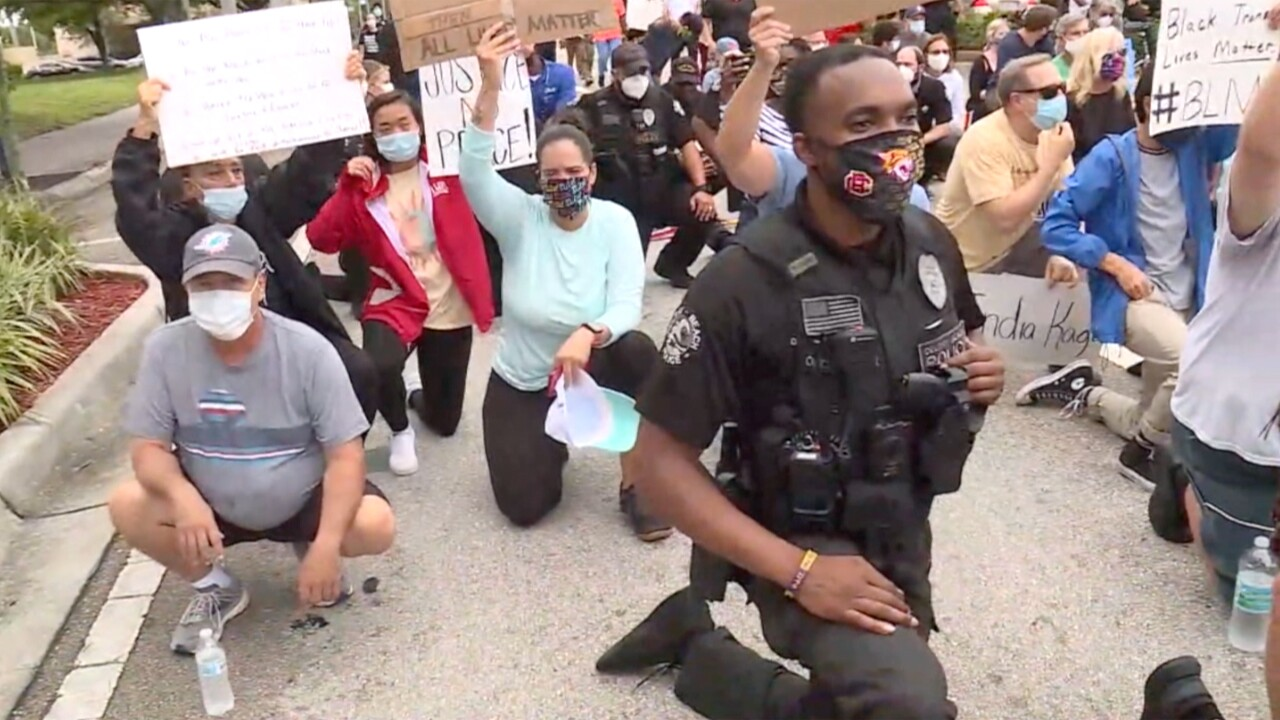 Delray Beach police officers walked with protesters and kneeled in solidarity during a protest on June 3, 2020.