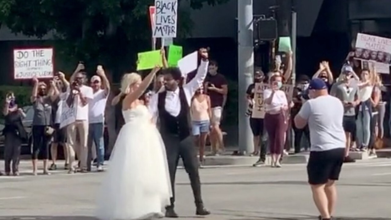 Bi-racial couple cheered on as they visit Black Lives Matter protest after wedding