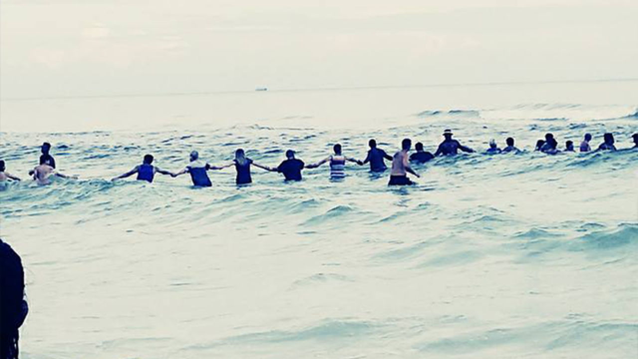 Beachgoers form human chain to rescue family