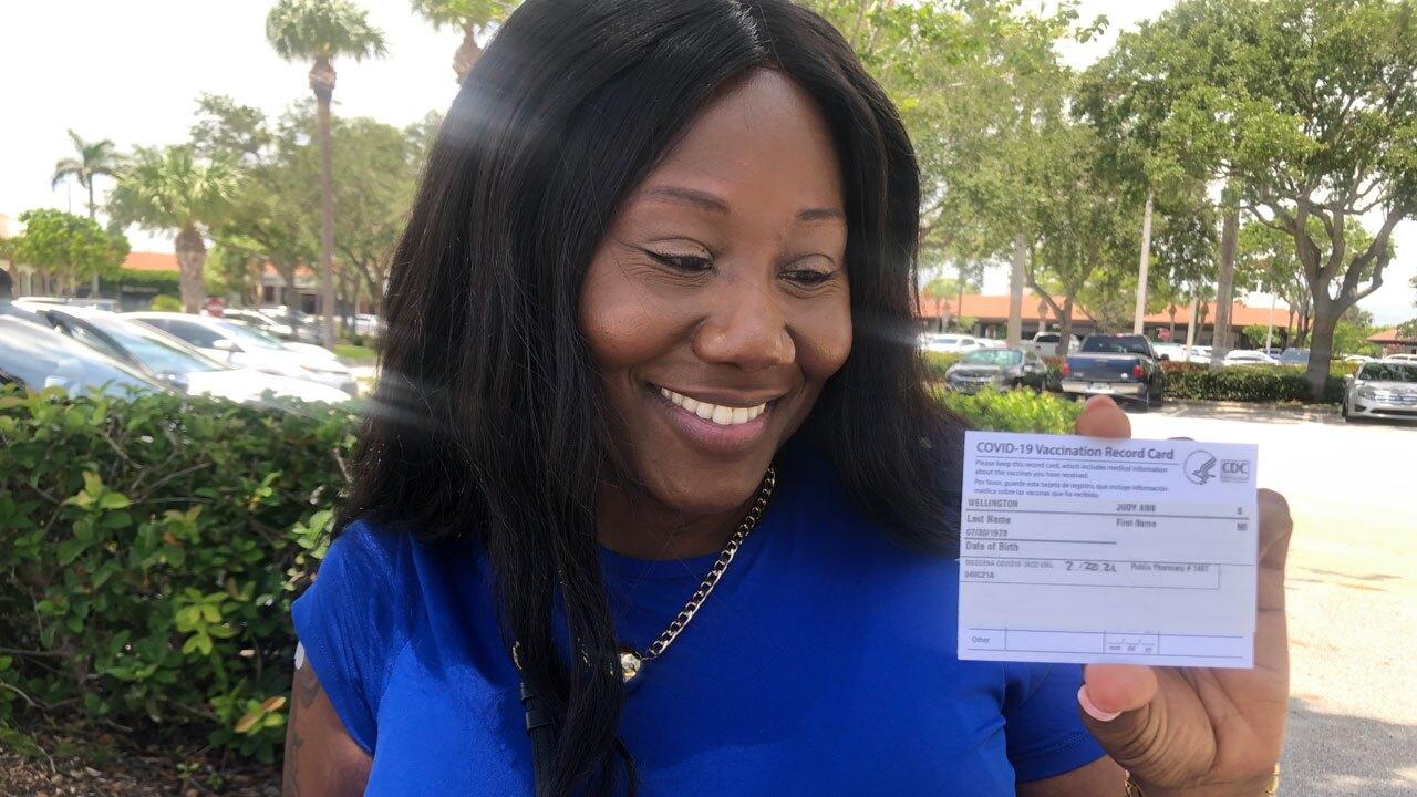 Nurse Judy-Ann Wellington shows off COVID-19 vaccine card on July 22, 2021