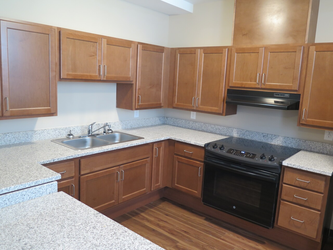 This photo shows a kitchen in one of the Logan Towers apartments. The kitchen has solid-surface countertops, a stainless steel sink and a black stove.