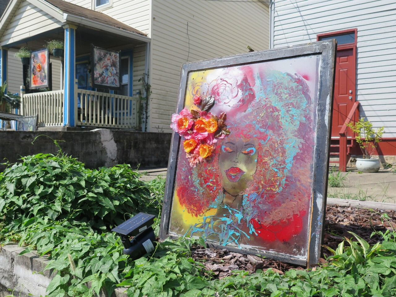 This photo features the window painted by Tashariea Harris and Nina Edwards with Edwards' home on the left. The window that Harris helped create has a portrait of a brown-skinned woman with red, blue and yellow hair.