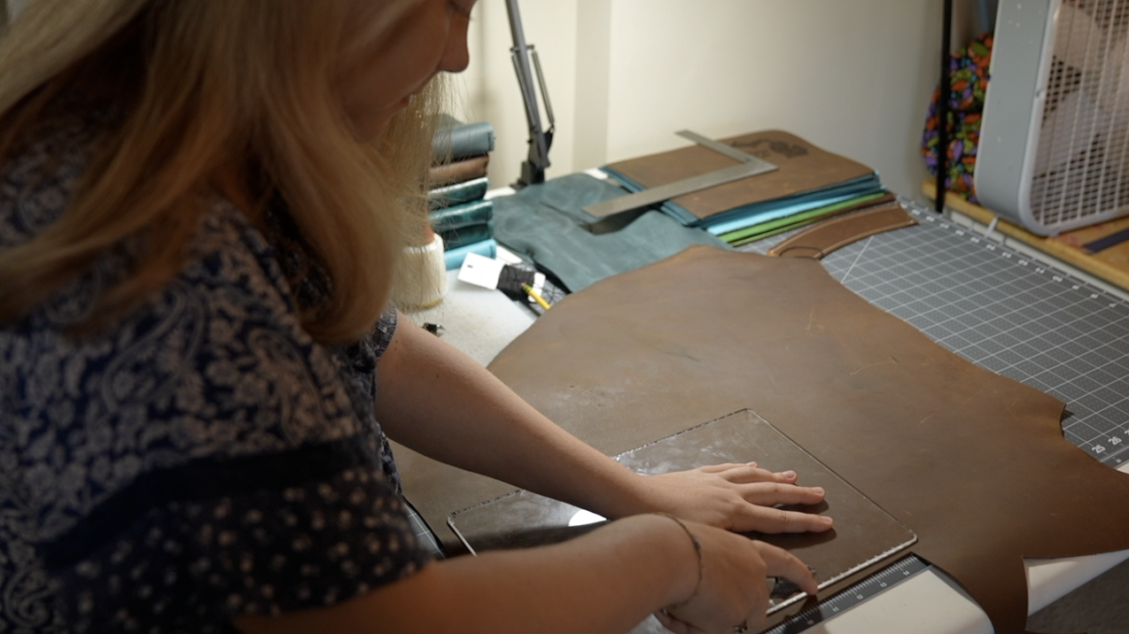 Evelyn cutting the leather using a template she created
