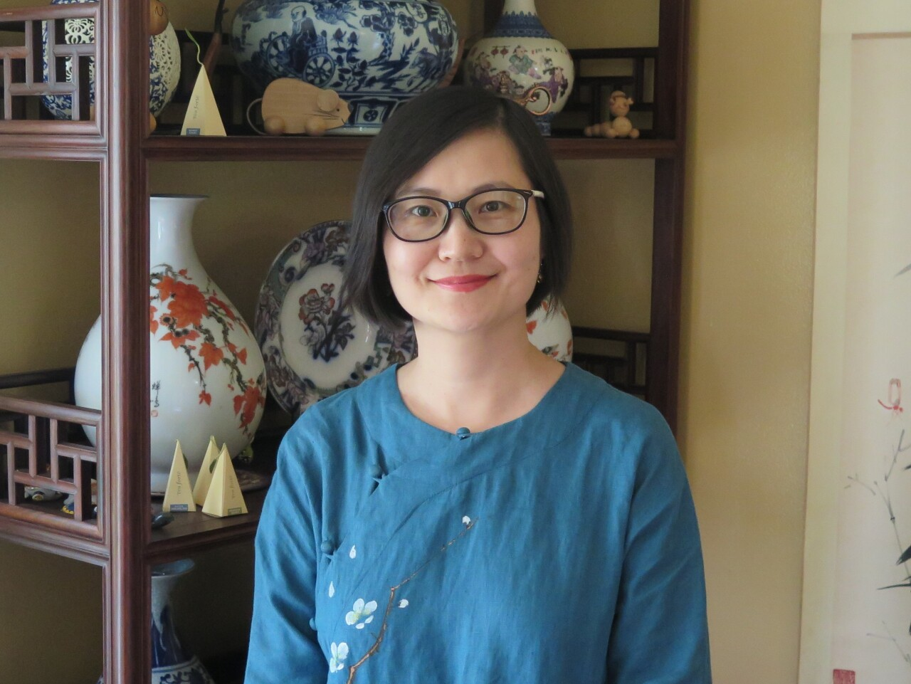 Felicity Tao is smiling in this photo. She has black, chin-length hair and is wearing glasses and a blue, embroidered top.