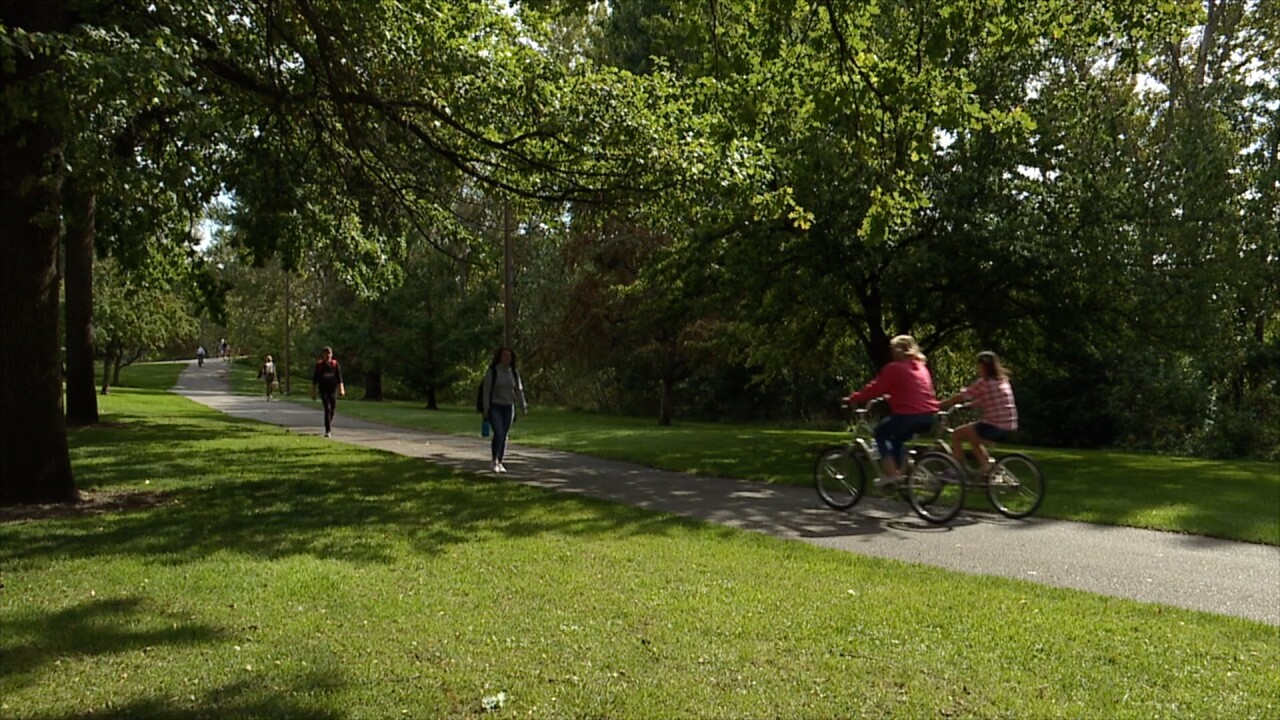 People walking and riding bikes on the Boise River Greenbelt near Zoo Boise.