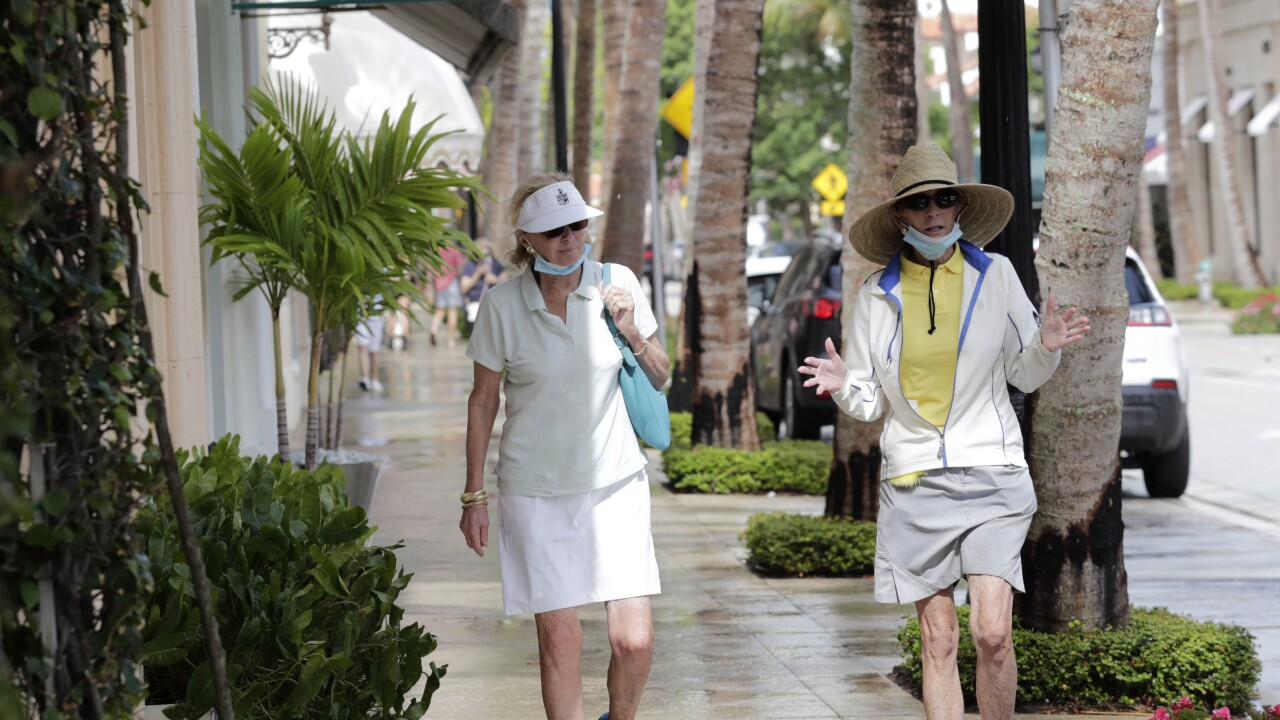 Couple wears mask while walking along Worth Avenue