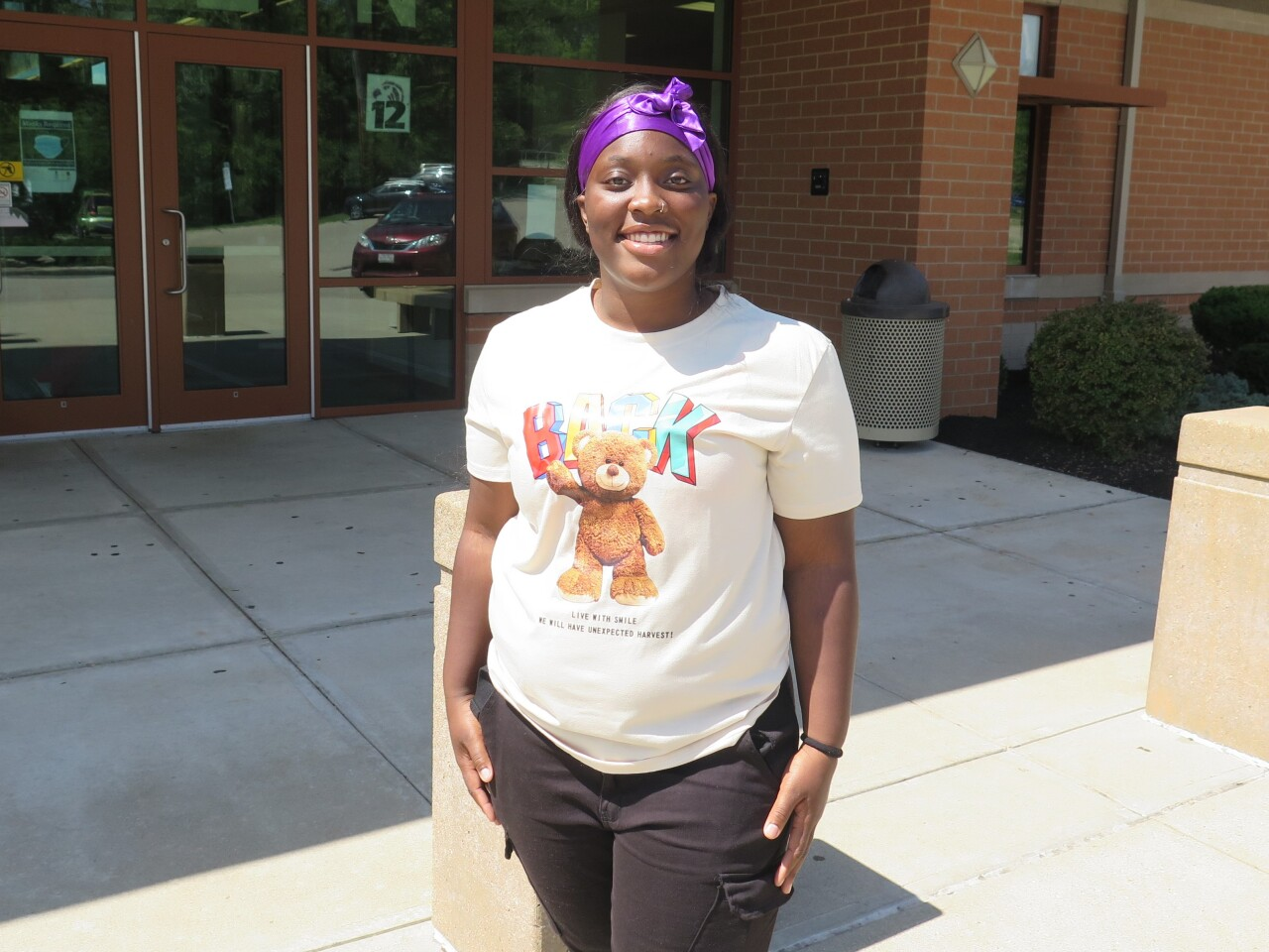 Teri'Ana Joyner smiles for a picture outside Aiken High School. Teri'Ana's long hair is pulled back by a purple scarf, and she's wearing a cream-colored t-shirt with a picture of a teddy bear on it.