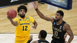 Michigan Wolverines guard Mike Smith drives to basket on Florida State Seminoles forward Malik Osborne and guard M.J. Walker in 2021 NCAA tournament