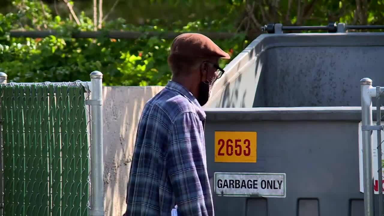 Robert Adams stands by dumpster and sign that reads 'Garbage Only'
