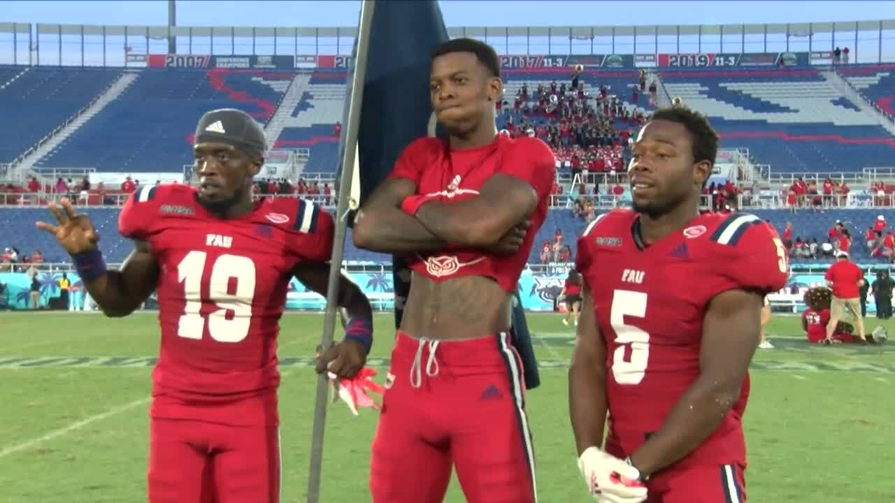 FAU Owls QB N'Kosi Perry celebrates with teammates after beating FIU Panthers in 2021