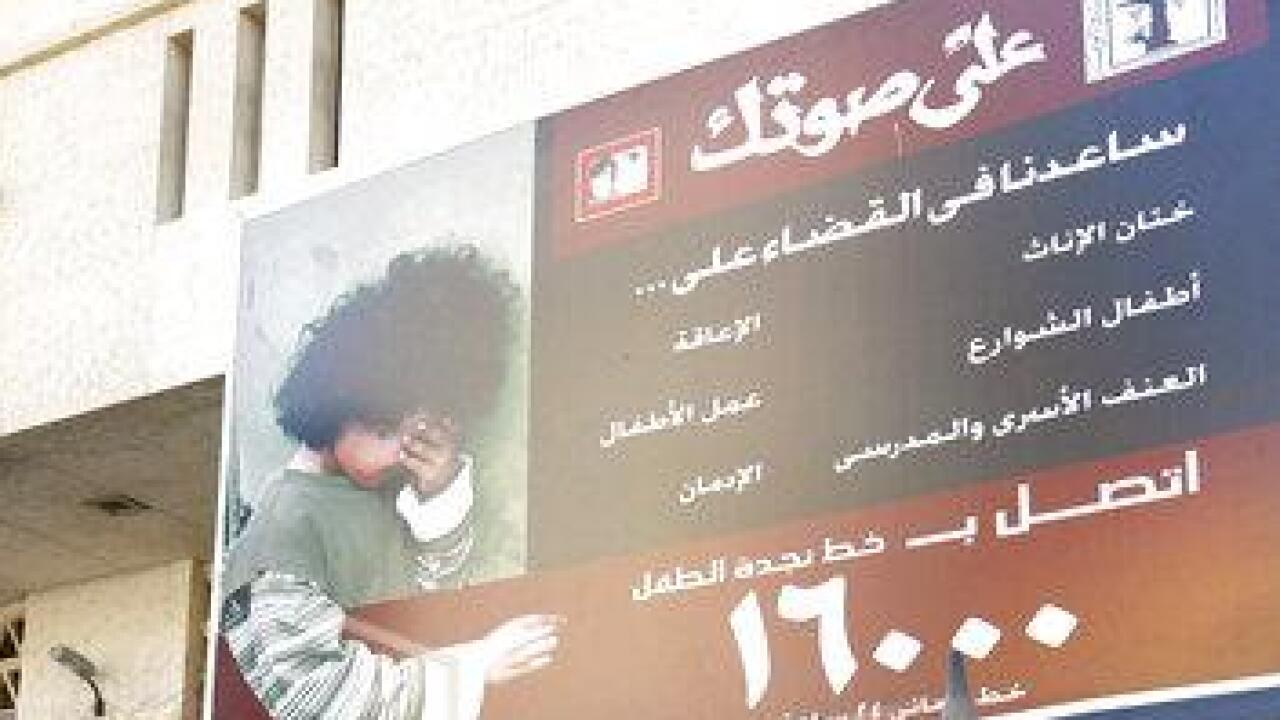 In this Dec. 5, 2007 file photo, Egyptian children walk under a billboard, that is part of a national campaign to encourage families to stop circumcising their daughters, outside the train station in the Upper Egyptian city of Minya. A 12-year-old girl died this week in southern Egypt after her parents brought her to a doctor who performed female genital mutilation, a criminal practice that remains widespread in the region, according to a judicial statement. The girl's death prompted Egypt's public prosecutor to order the arrests of her parents and the physician who preformed the procedure, also known as female circumcision, said the statement released late Thursday, Jan. 30, 2020 by the prosecutor's office. (AP Photo/Asmaa Waguih, File)