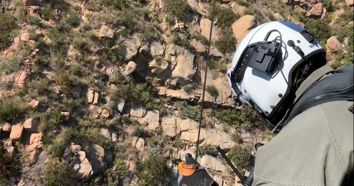 Emergency personnel rescue injured paraglider in mountains above Carpinteria