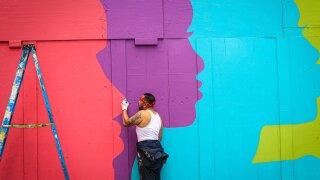 Local artist Glen Infante paints a mural at Public Square.