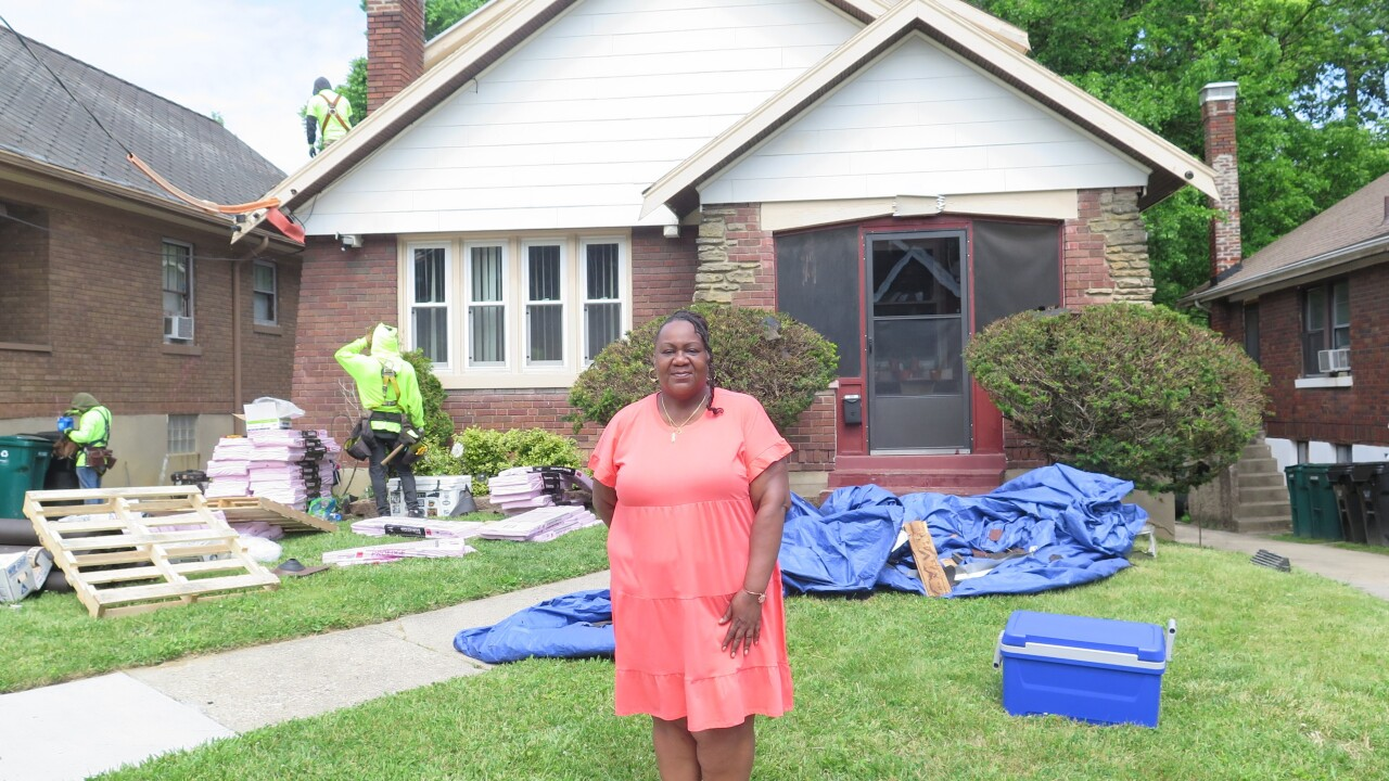 Naima Jackson poses in front of her two-story brick home on May 24, 2020, as a workers from Deer Park Roofing replace the roof on her house.