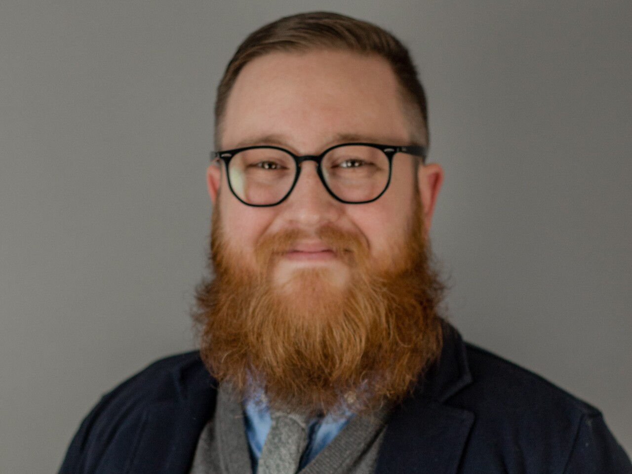 Justin Tucker is smiling in this portrait. He has a full, red beard and mustache and short-cropped hair. He's wearing glasses, a blue shirt and a gray tie with a gray sweater and dark blazer.