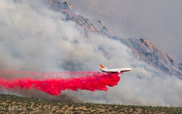 A plane drops fire retardant on the lower slopes of the Bighorn Fire in the Catalina Mountains