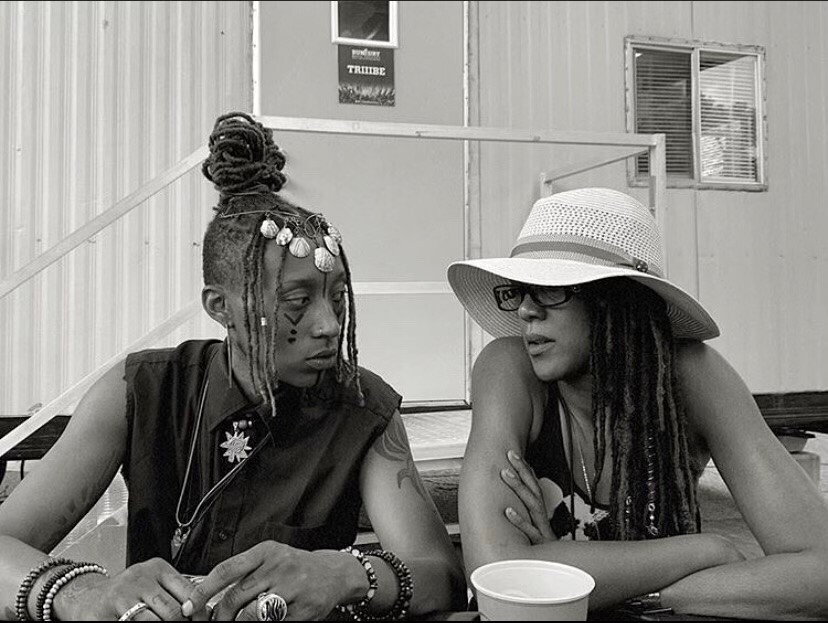 In this undated photo, Siri Imani, on the left, is looking at her mom, Jennie Wright, as they sit next to each other. Imani is wearing her braided hair in a pile on top of her head, and her face is painted. Wright's long braids hang down below her straw hat.