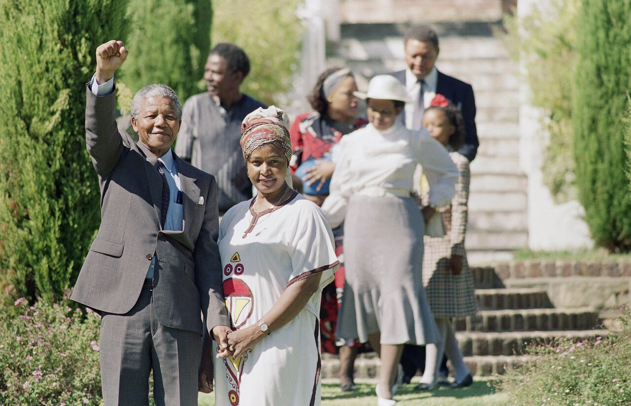 A smiling Nelson Mandela, released African National Congress leader, gives a black power salute at Archbishop Desmond Tutu's residence in Cape Town, South Africa, Feb. 12, 1990. Mandela was freed from prison after serving over 27 years. At right is his wife Winnie Mandela. (AP Photo/Ada Brodlow)