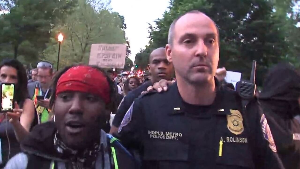 Protesters walking with officers.JPG