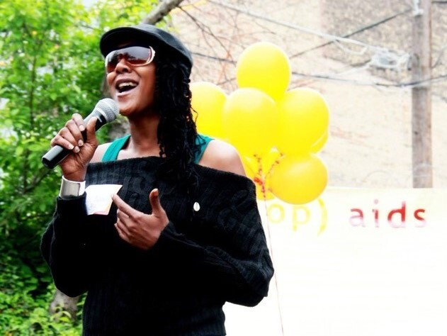 Jennie Wright speaks into a microphone on a sunny day in an undated photo. She is wearing a black cap and sunglasses, and yellow balloons appear in the photo behind her.