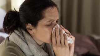Ill woman sneezing in a tissue