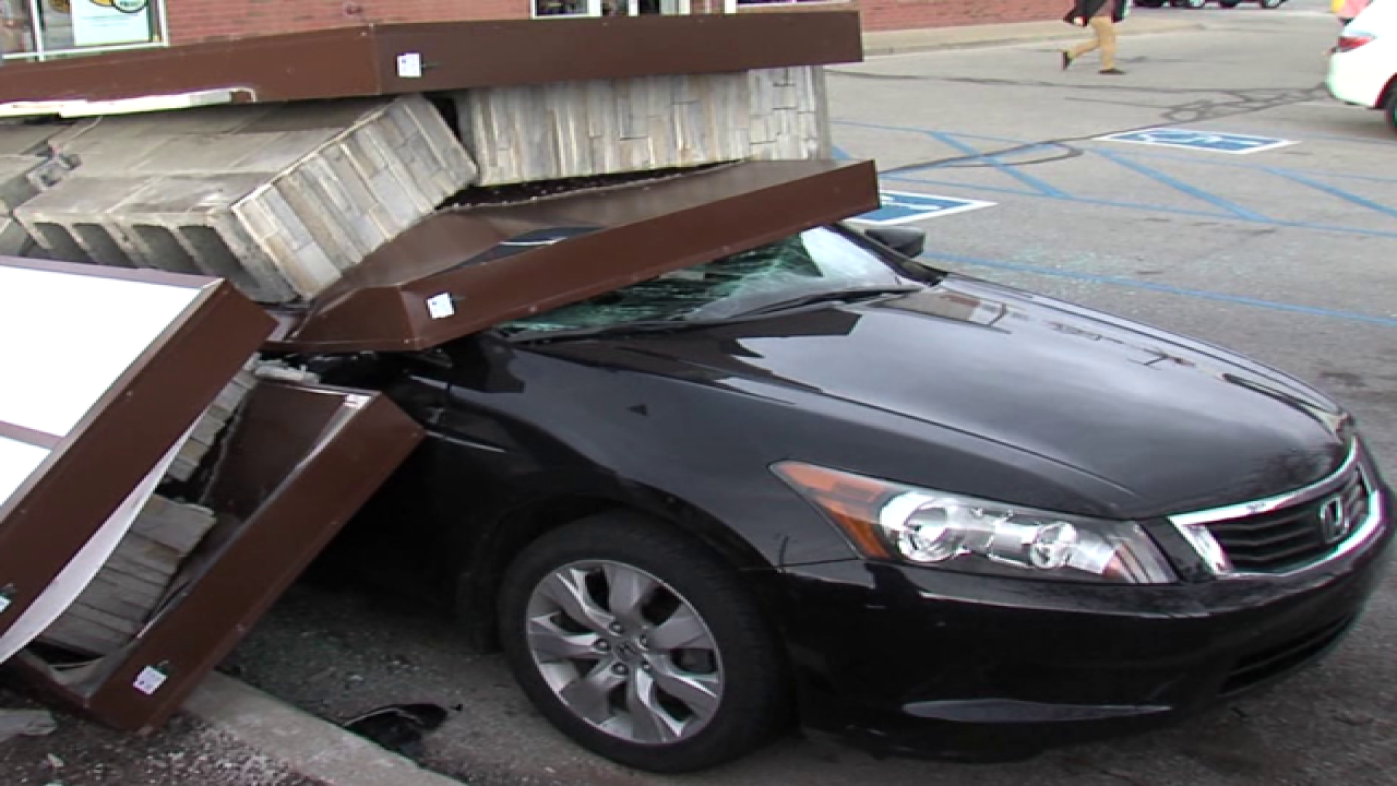 PICS: Sign falls on car, driver gets out