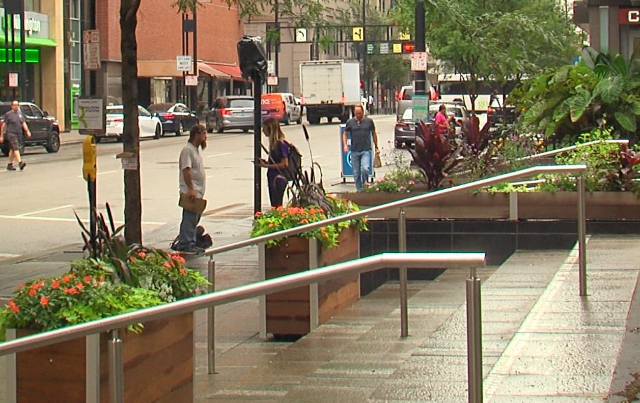 A GeneroCity 513 street outreach worker talks with a man panhandling at Fountain Square.