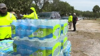 Crews hand out cases of water bottles at Gaines Park in West Palm Beach on June 1, 2021.jpg