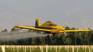 A crop duster airplane sprays pesticide