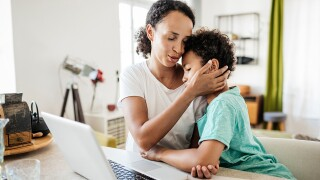 Single Mom Affectionately Holding Son While Working From Home