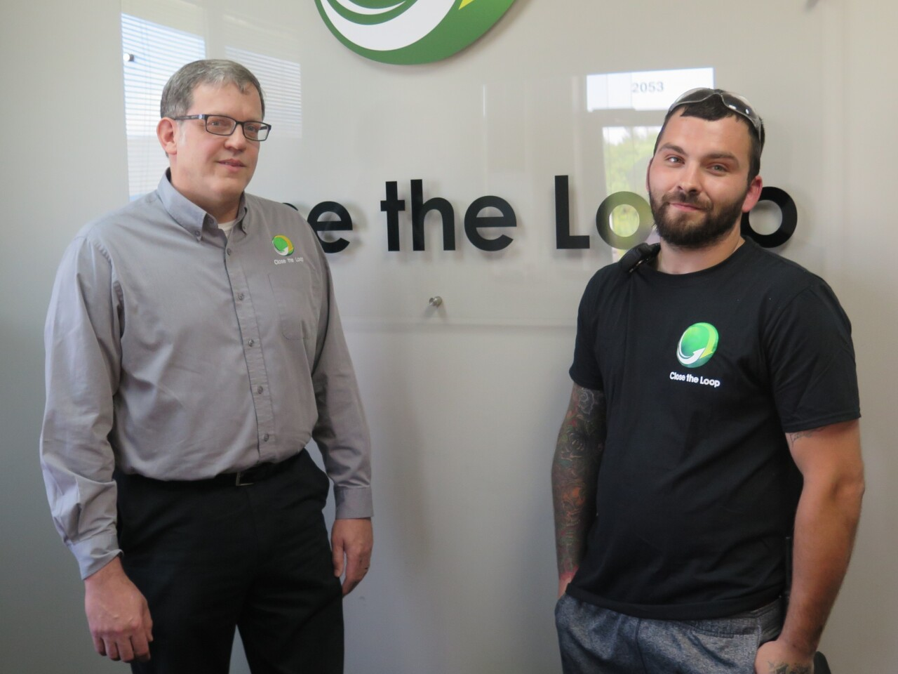Close the Loop co-CEO Tom Ogonek, at left, poses for a photo with Adam Criss. They are standing in front of a company logo that says Close the Loop.