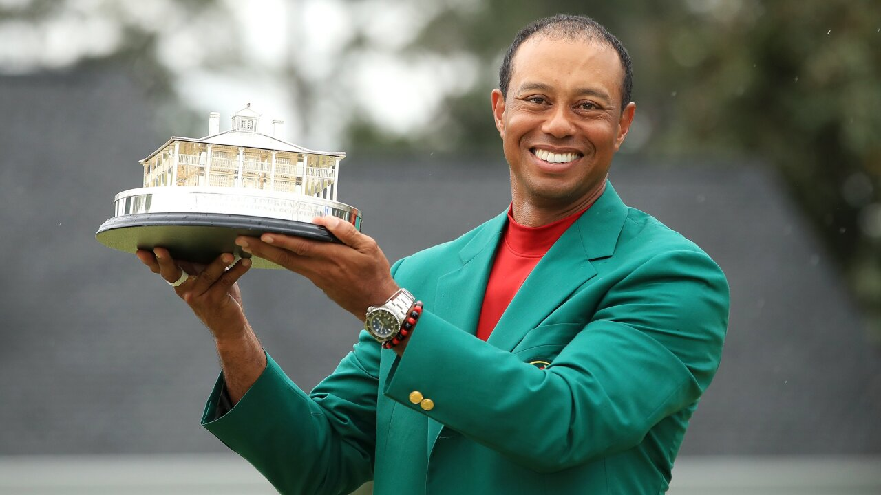 tiger woods smiles with masters trophy while wearing green jacket