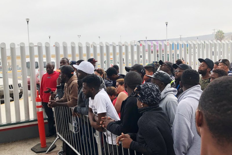 In this Sunday, July 28, 2019, photo, migrants in Tijuana, many from Cameroon, listen to names being called for those who can claim asylum that day in the US. English-speaking Cameroonians fleeing atrocities of their French-speaking government helped push Tijuana's asylum wait list to 10,000 on Sunday, up from 4,800 just three months earlier. (AP Photo/Elliot Spagat)