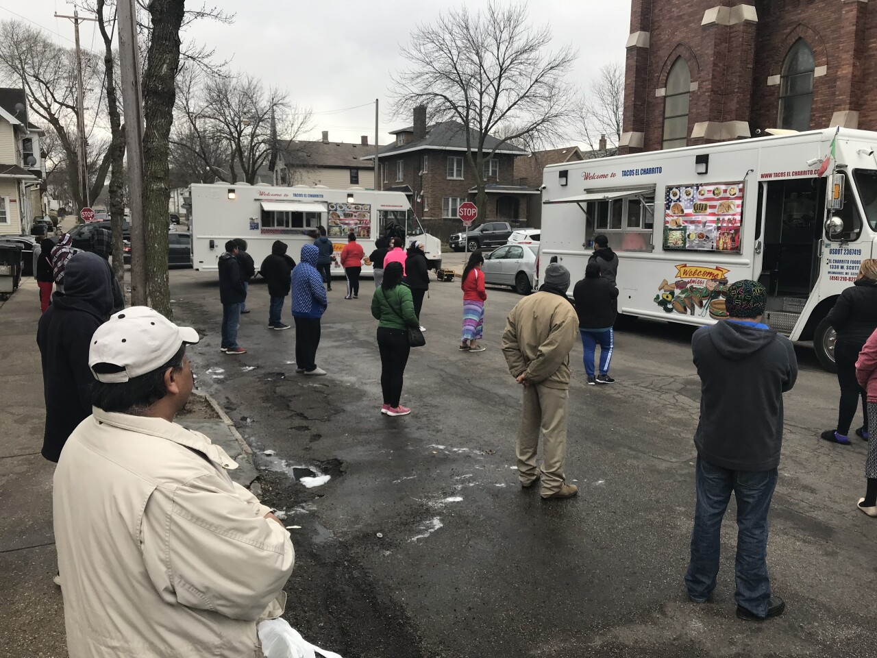 People do their best to stay 6 feet apart while waiting for their tacos at the corner of 14th and Scott Streets in Milwaukee.