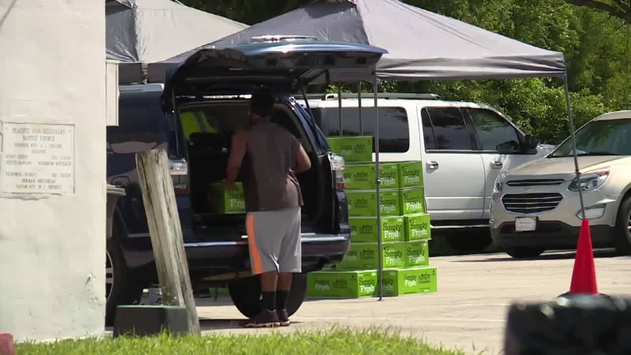 man packing Farmers to Families food boxes into vehicles