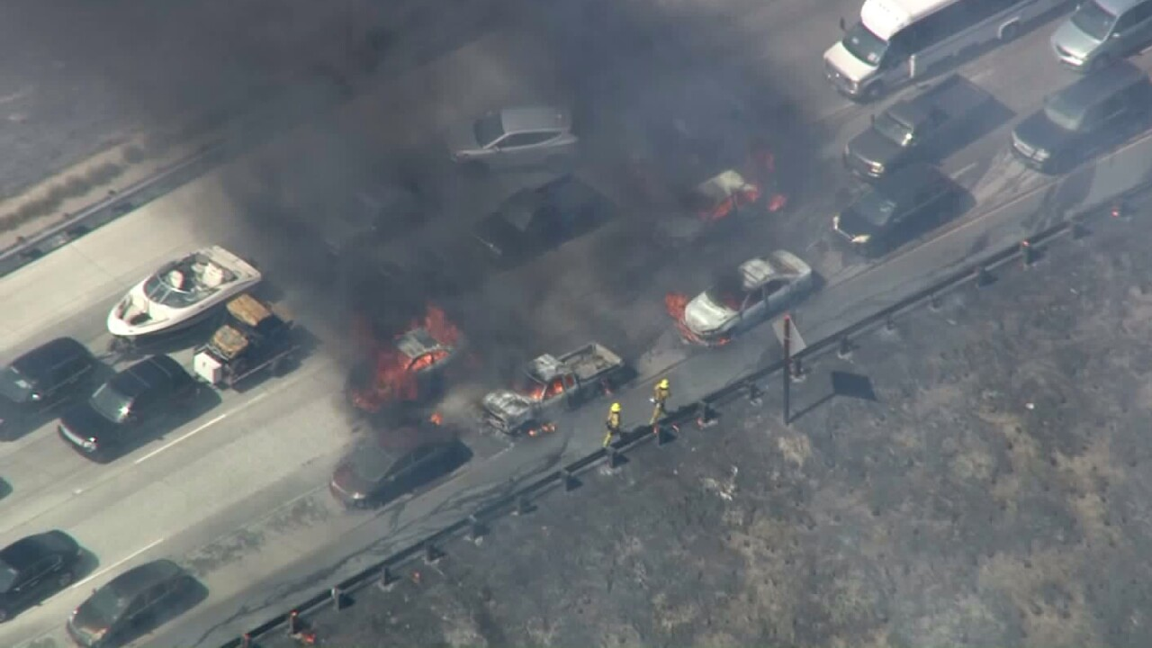 Cars set ablaze as wildfire jumps California freeway