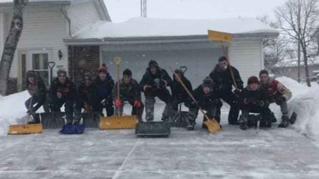 Lomira High School's wrestling team poses after shoveling a neighbor's driveway.